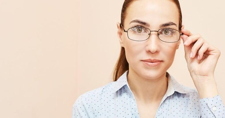 Primer plano de una mujer de ojos verdes usando anteojos aprendiendo sobre sinónimos en inglés