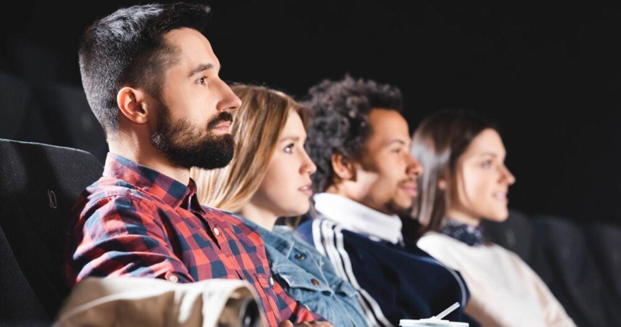 Amigos en el cine viendo una película y usando sinónimos en inglés