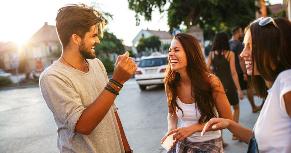 Jóvenes riendo al sol practicando verbos en inglés