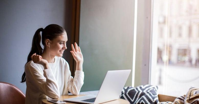 Mujer joven aprendiendo inglés feliz con un curso de inglés online en su laptop.