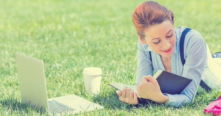 Mujer joven sonriendo acostada sobre el pasto con su laptop y un libro estudiando los verbos regulares e irregulares en inglés