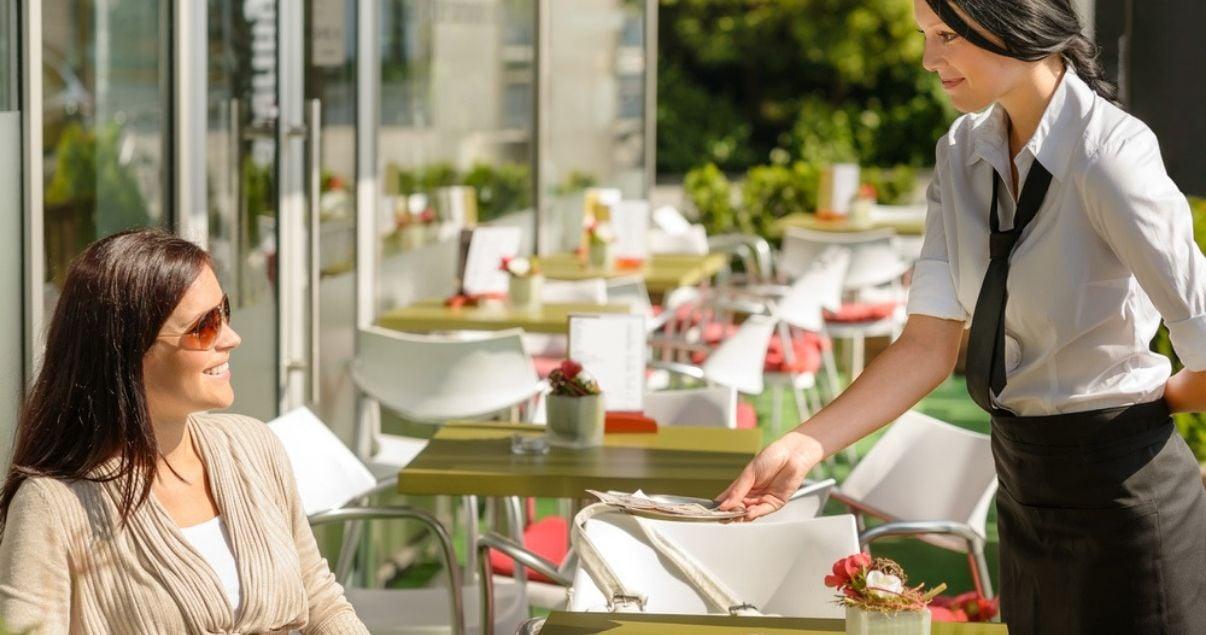 Una moza entregando la cuenta a una mujer después de haber disfrutado de una comida en inglés.