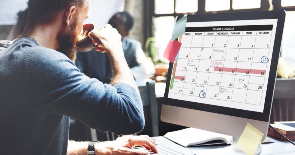 hombre en sweater sentado en la oficina con calendario para planificar aprender inglés