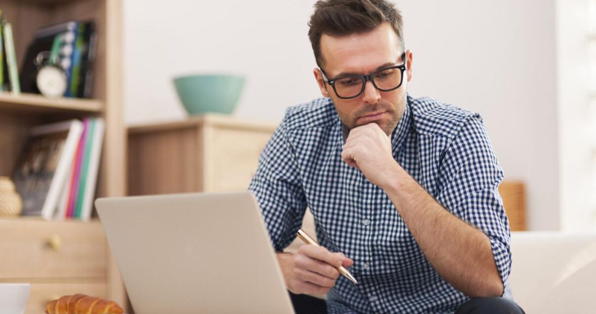 hombre con laptop pensando en aprender inglés