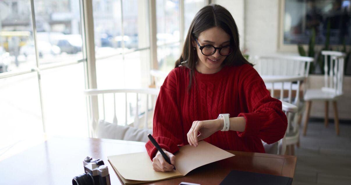 mujer joven sentada en un café mirando hora para aprender inglés