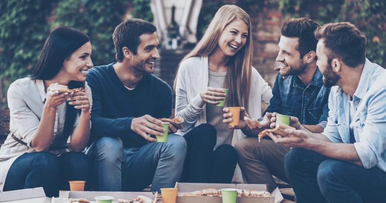 Amigos almorzando riendose mientras se comunican utilizando vocabulario en inglés