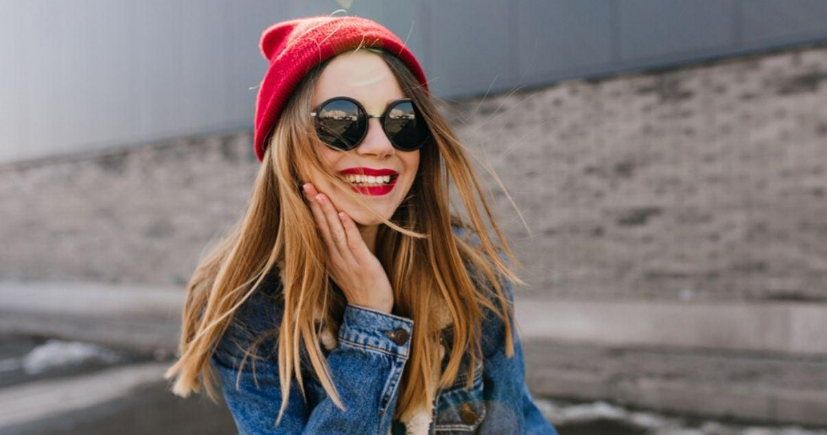 Mujer joven con gorro rojo sonriendo con lentes de sol aprendiendo modismos en inglés sobre partes del cuerpo