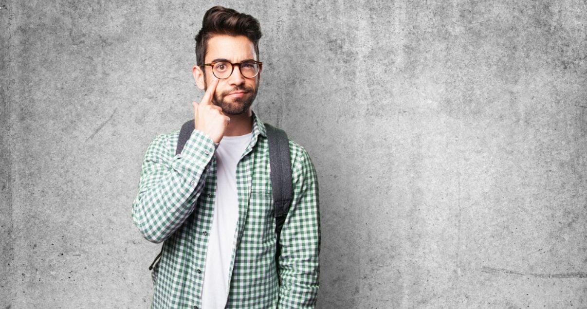 Hombre jóven con anteojos señalando su ojo aprendiendo modismos en inglés sobre partes del cuerpo con Wall Street English