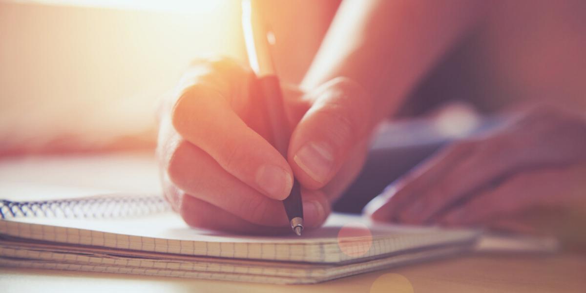 Foto artística de una persona escribiendo en su cuaderno para aprender inglés.