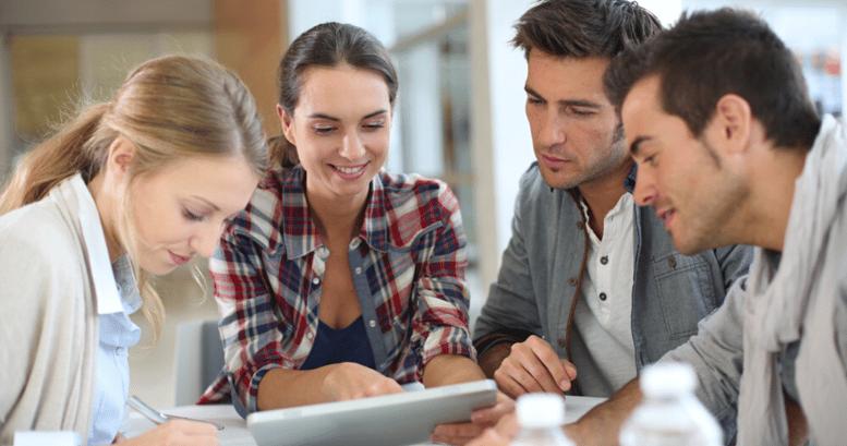Grupo de adultos aprendiendo juntos nuevo vocabulario en inglés desde una tablet.