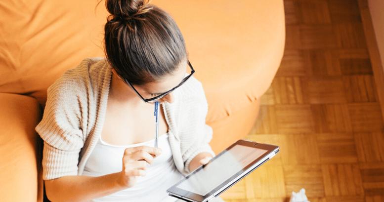 Mujer joven comenzando a aprender inglés desde su tablet en la comodidad de su sillón.