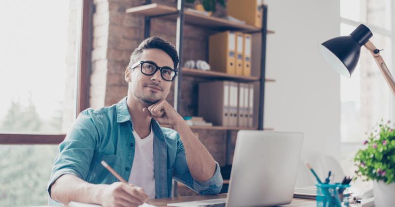 Un hombre joven sentado con su laptop y un cuaderno pensando si le conviene utilizar tecnología para aprender inglés.