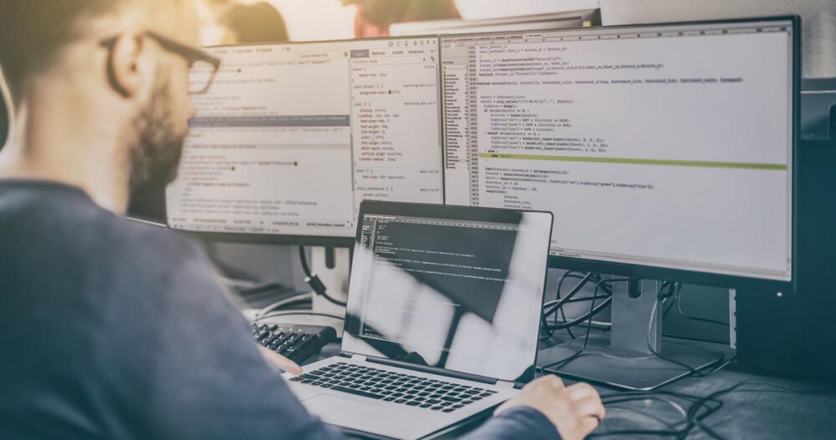 Ingeniero informático trabajando con computadoras utilizando sus habilidades para hablar inglés para programar.