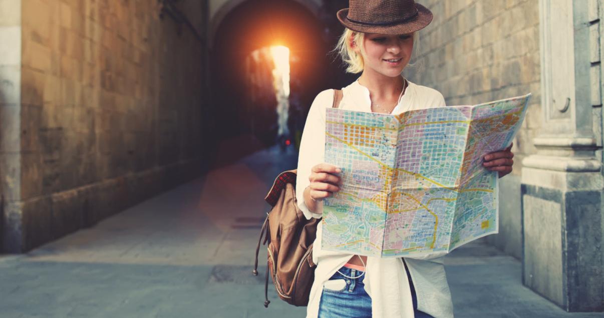 Joven mujer utilizando el inglés para viajar con un mapa en las manos.