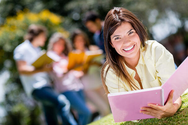 Beautiful college girl studying outdoors and looking happy