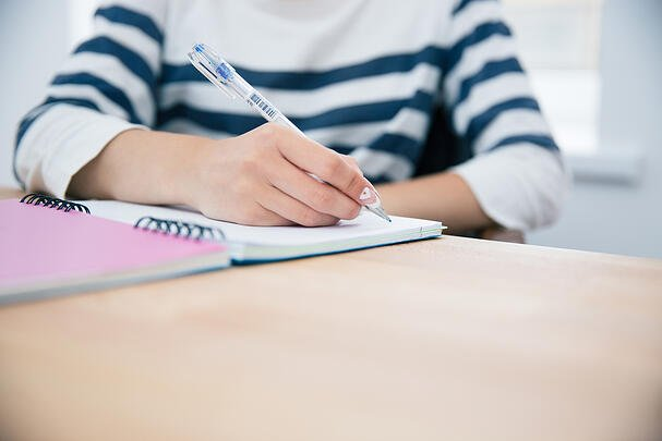CLoseup portrait of a woman writing in notepad at office