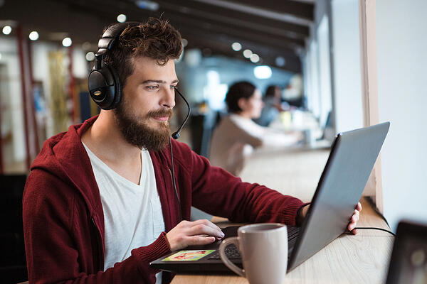 Concentrated handsome male with beard using headset and laptop-1