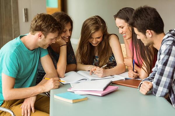 Smiling friends sitting studying together after school