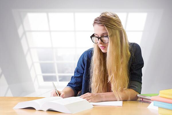 Student studying in the library against room with large window showing city