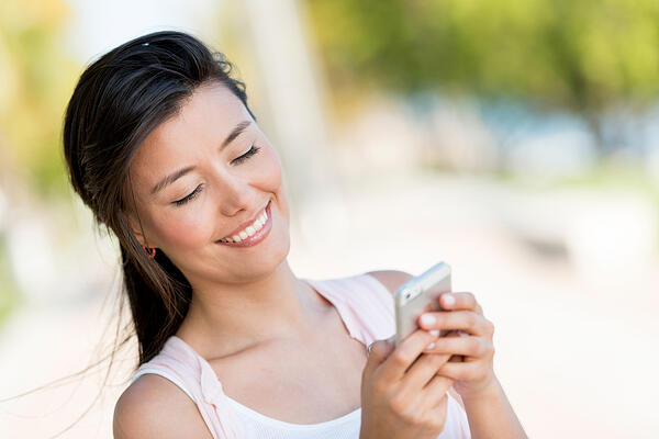 Woman texting on a smart phone looking happy
