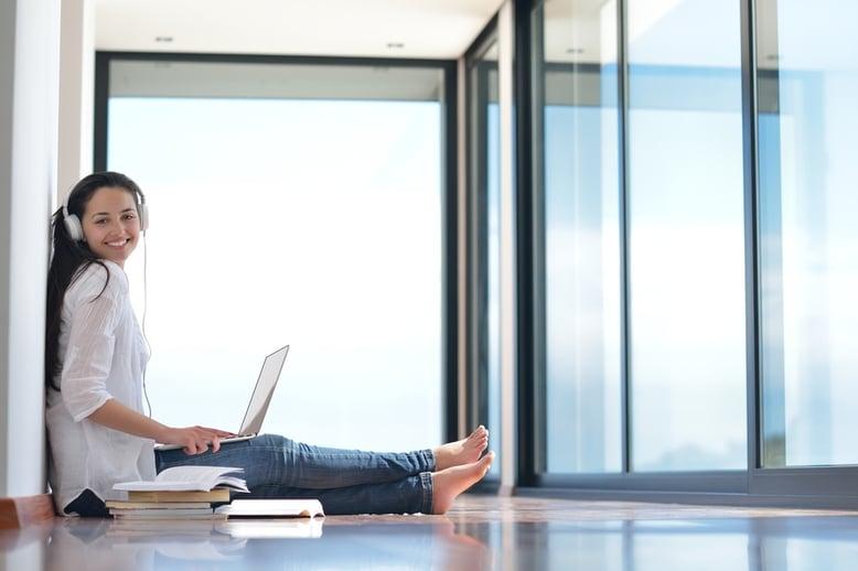 Mujer aprendiendo inglés desde su laptop, entrenando su oído.