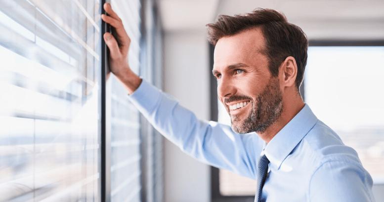 Trabajador vestido de traje mirando por la ventana feliz porque puede hablar en inglés con clientes y colaboradores