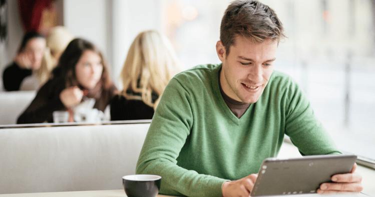 Un hombre concentrado con su ipad en un cafe aprendiendo sobre gramática en inglés