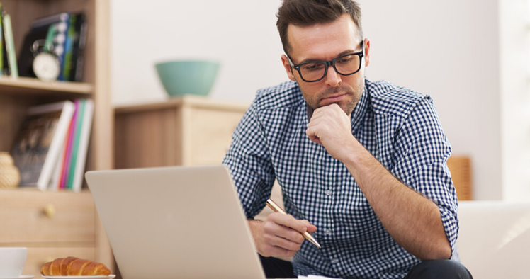Un hombre concentrado con su laptop y un cuaderno aprendiendo sobre gramática en inglés