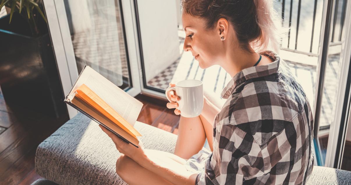 Una joven mujer leyendo un libro con una taza de cafe para prepararse para su examen toefl.