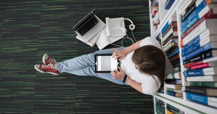 Una mujer con su computadora en una biblioteca estudiando vocabulario en inglés