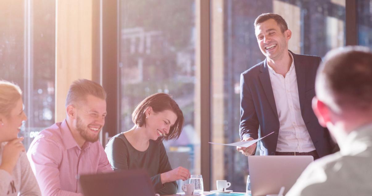 hombre hablando en ingles para el trabajo en reunion de oficina con colegas felices