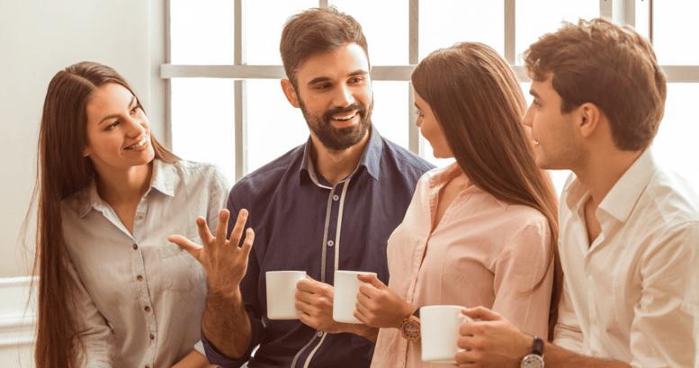 hombre hablando felizmente en ingles para el trabajo con colegas y tomando cafe en el pasillo de la oficina