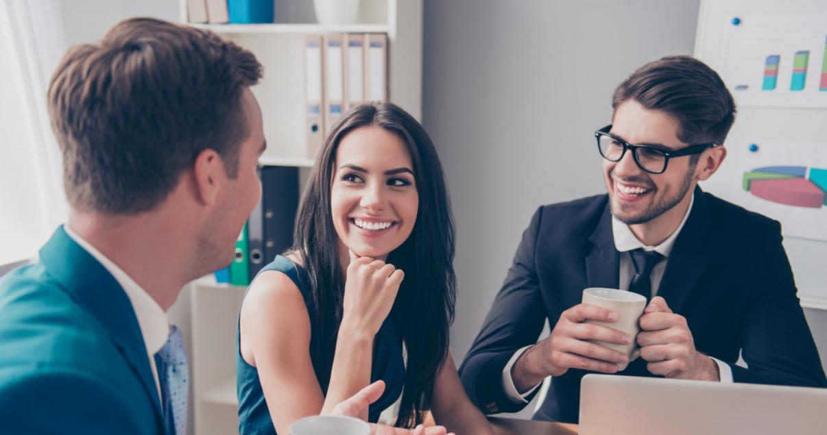 mujer sonriente hablando con dos colegas hombres utilizando ingles para el trabajo en la oficina