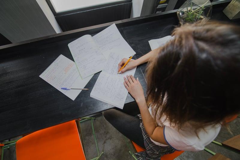 girl-sitting-table-writing