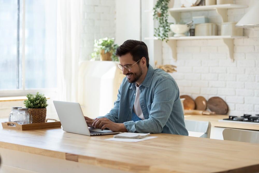 Hombre sentado en la cocina estudiando inglés online