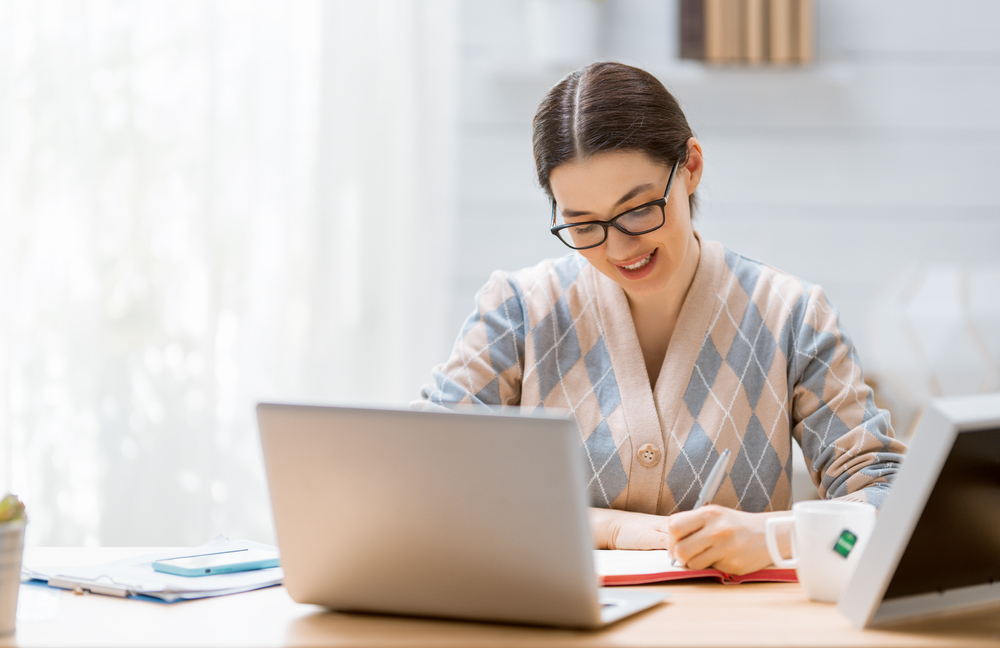 chica sentada aprendiendo ingles online desde su computadora