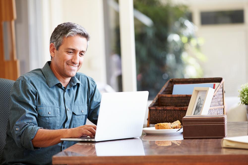 Hombre sentado desayunando aprendiendo ingles online desde su casa