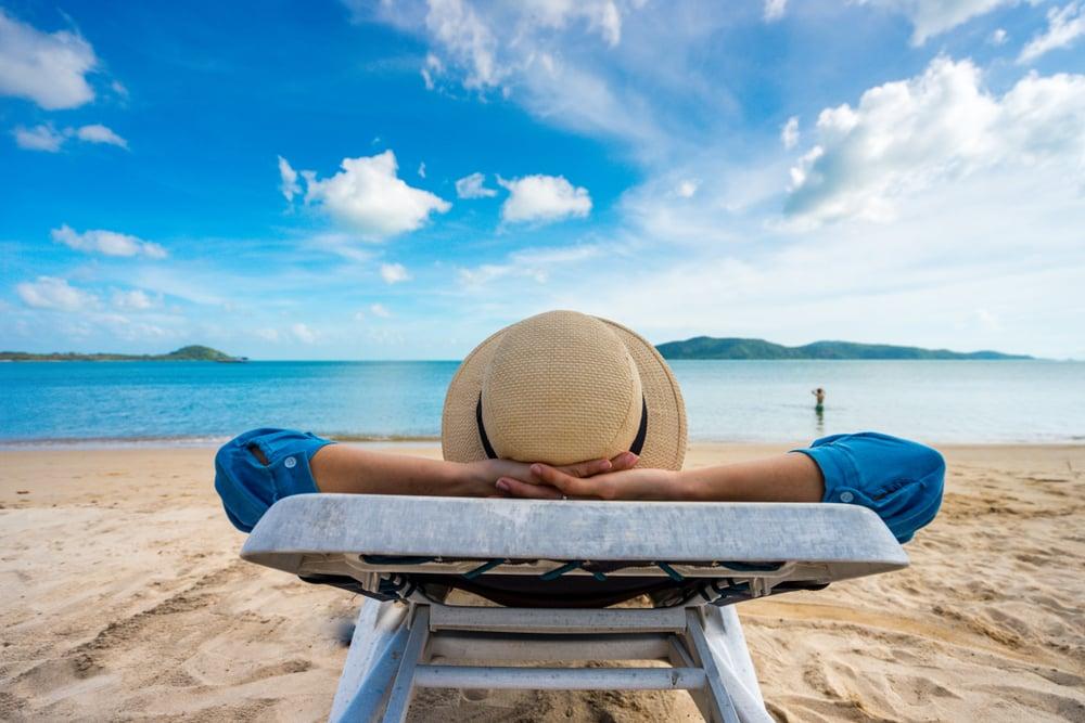Joven en la playa relajada porque sabe que está de vacaciones y aprende Inglés online de forma fácil y divertida